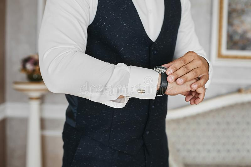 Close view of the luxury watches on the hand of a handsome businessman in a tuxedo and in a shirt with cufflinks.  stock photo