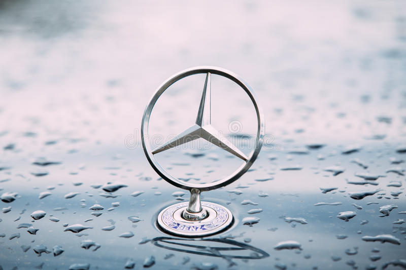 Close View Of Metal Star Logo Of Mercedes Benz At Wet Hood Of Blue stock image