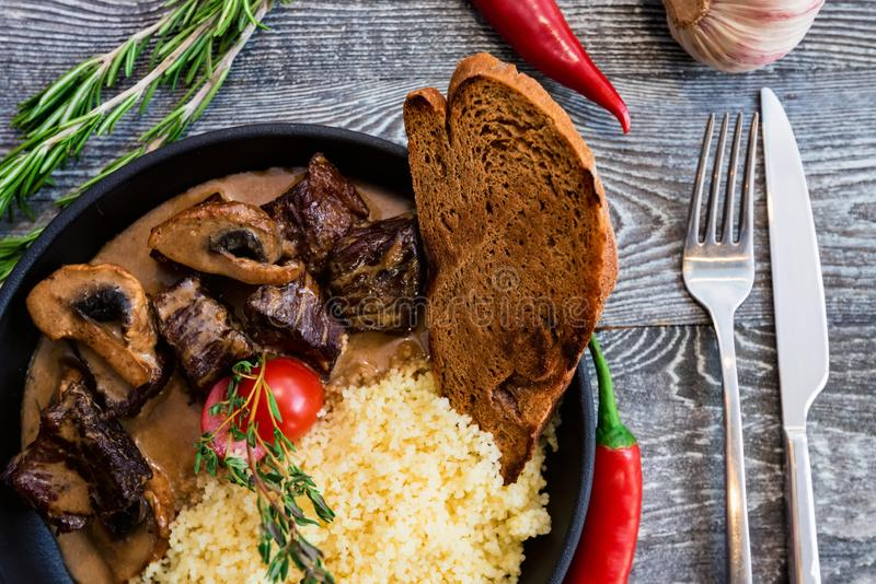 Close view mushroom beef stroganoff in frying pan with couscous stock photo