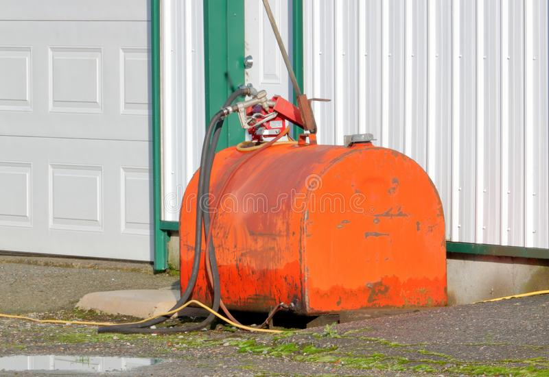 Industrial Fuel Tank and Hose. Close view of an old petrol or fuel storage tank used in an industrial yard stock photography