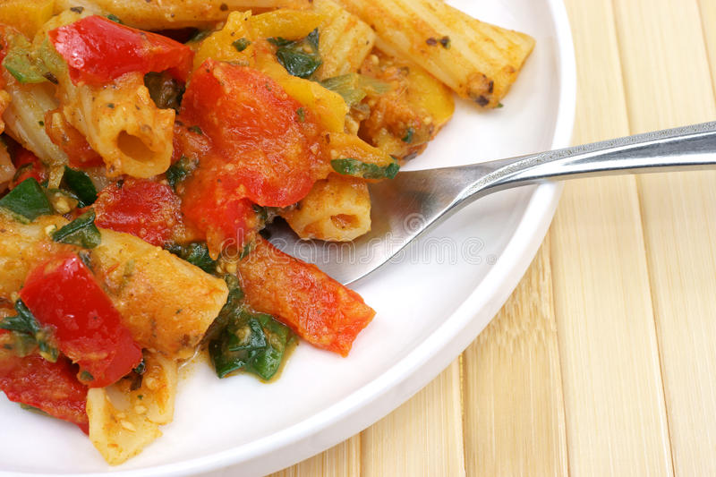 Close view of a rigatoni meal. A close view of a rigatoni pasta meal with peppers and spinach on a small plate with a fork stock photography