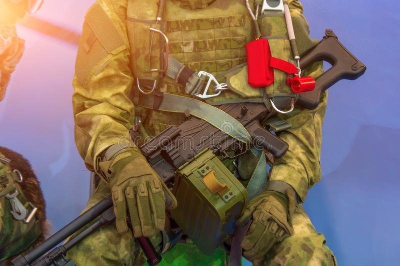 Close view of a seated soldier in military clothes and weapons in his hands royalty free stock image
