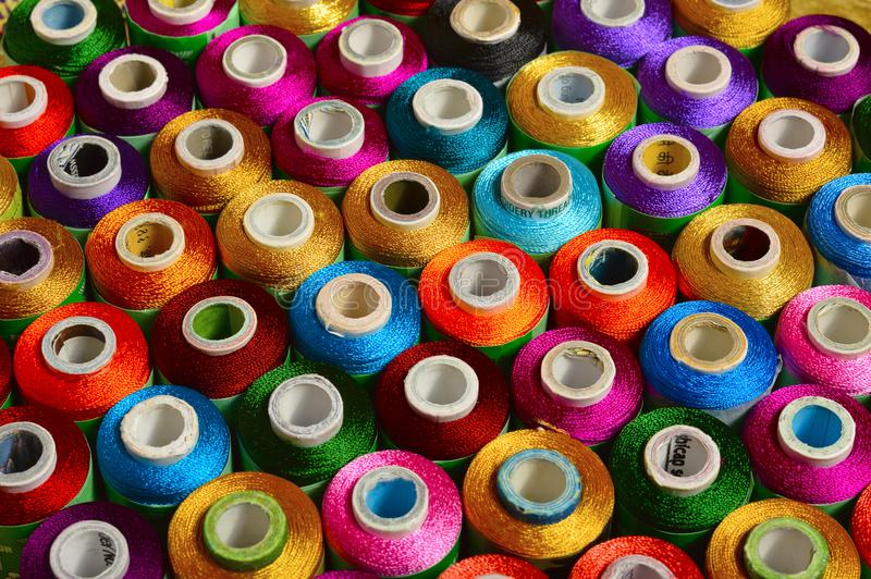 Sewing threads of various color on spindles royalty free stock photos