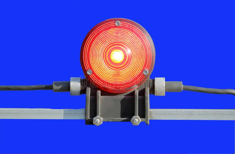 Train Crossing Light With Chromatic Background. Close view of a train crossing light flashing red with a chromatic blue background royalty free stock photography