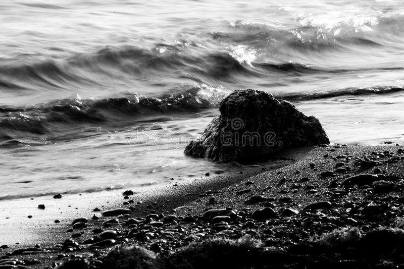 A close view of water on a lake shore, with details of sands and little and big stones royalty free stock photo