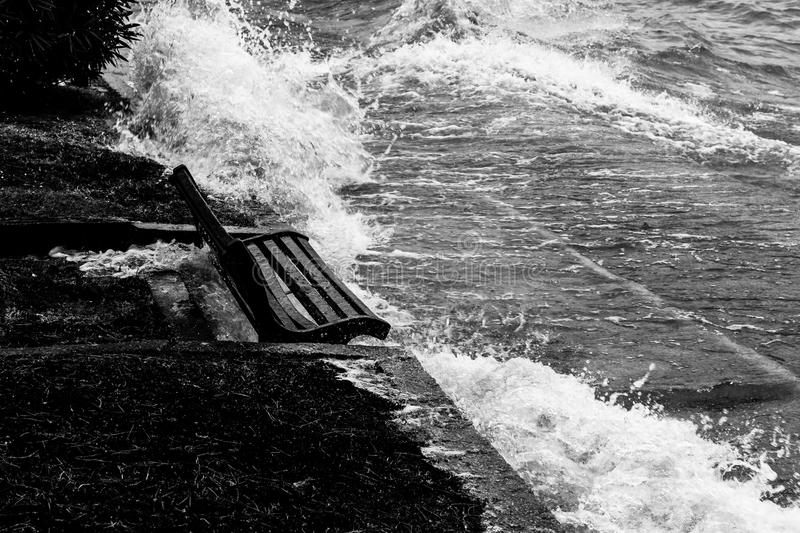 Close view of water splashing on a sitting bench near a lake shore stock image