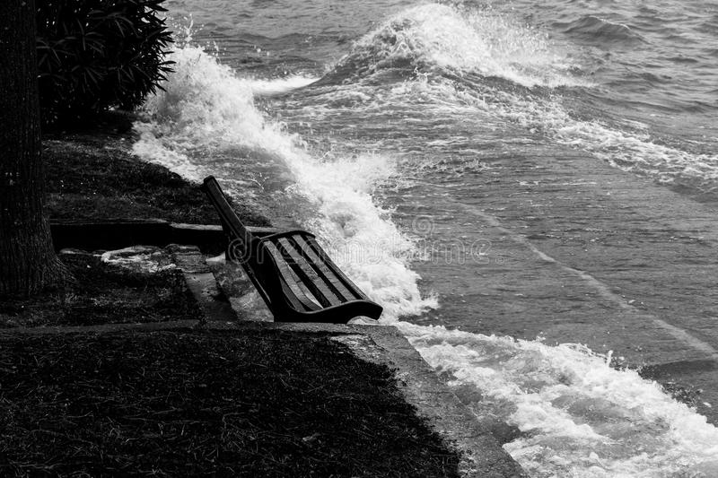 Close view of water splashing on a sitting bench near a lake shore stock photography