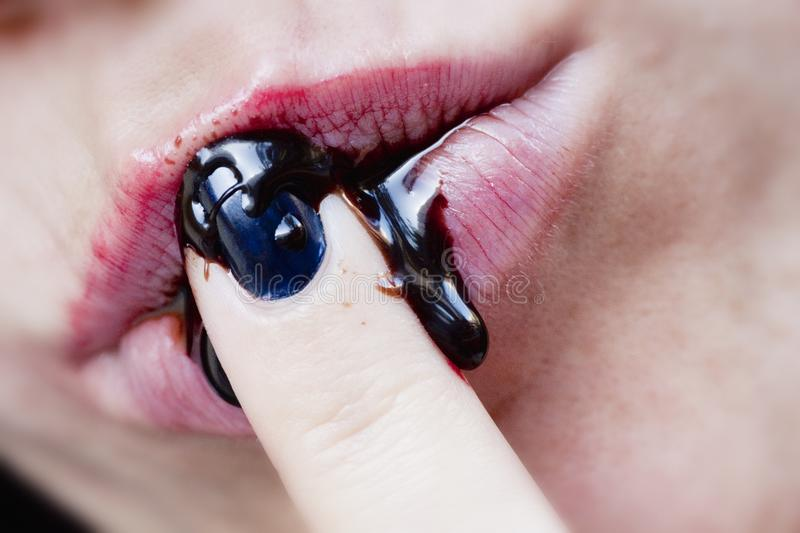 Woman sucks finger. Close view of a woman lips sucking a finger filled with chocolate royalty free stock photos