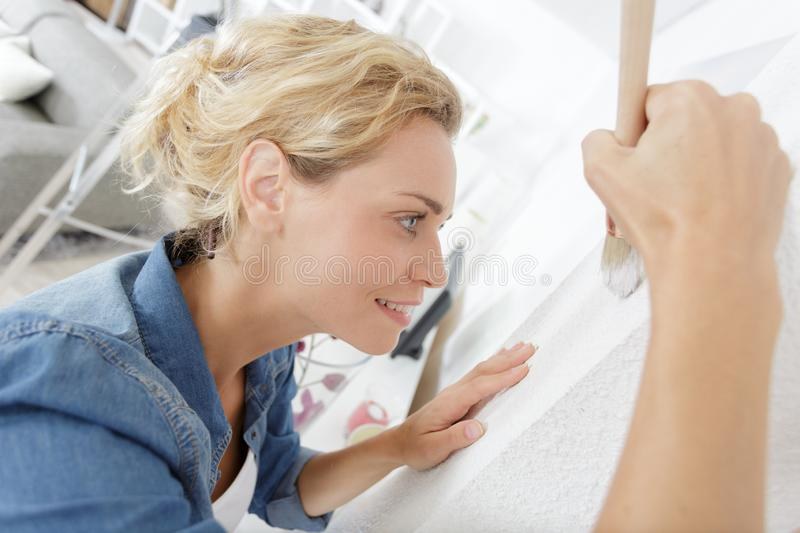 Close view woman touching up paint on wall stock photography