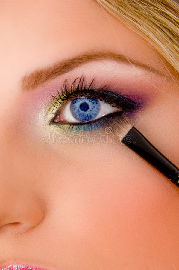 Close view of young model putting eyeliner stock image