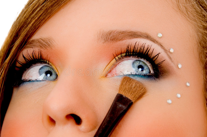 Close view of young woman putting eyeliner stock images
