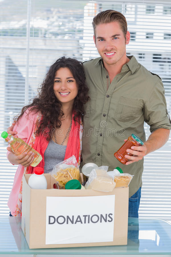 Close volunteers taking out food from donations box royalty free stock image