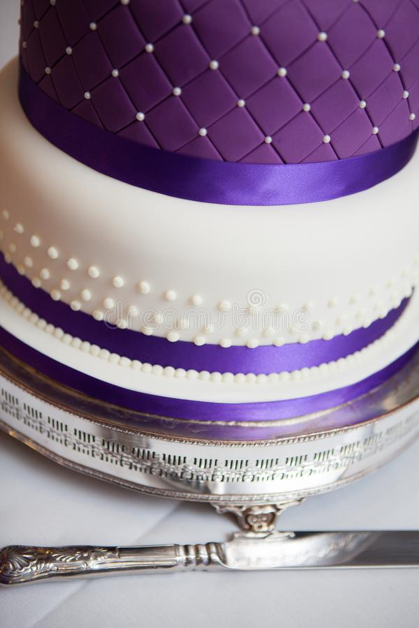 A close of a wedding cake with purple ribbon stock photos