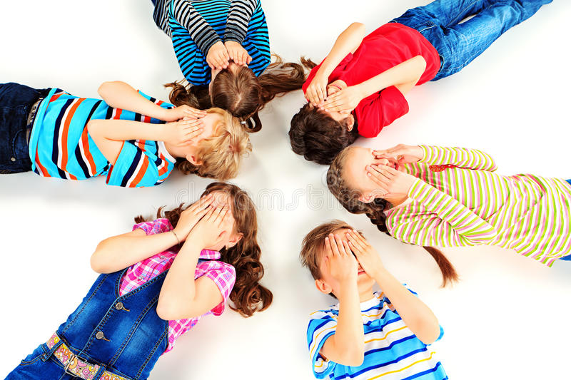 Close your eyes. Group of children lying on a floor and covering their faces with their hands. Isolated over white stock image