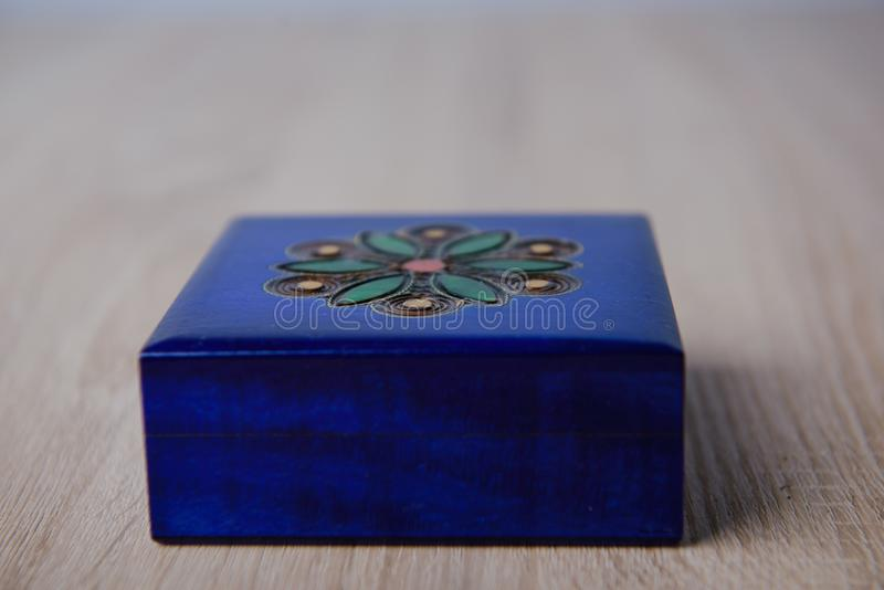 closed antique wooden blue jewelry box on the table stock photography