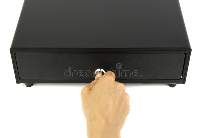 Closed black cash drawer or cashbox and hand with key in lock, top view white background. Concept of finance audit or commerce inspection royalty free stock photography