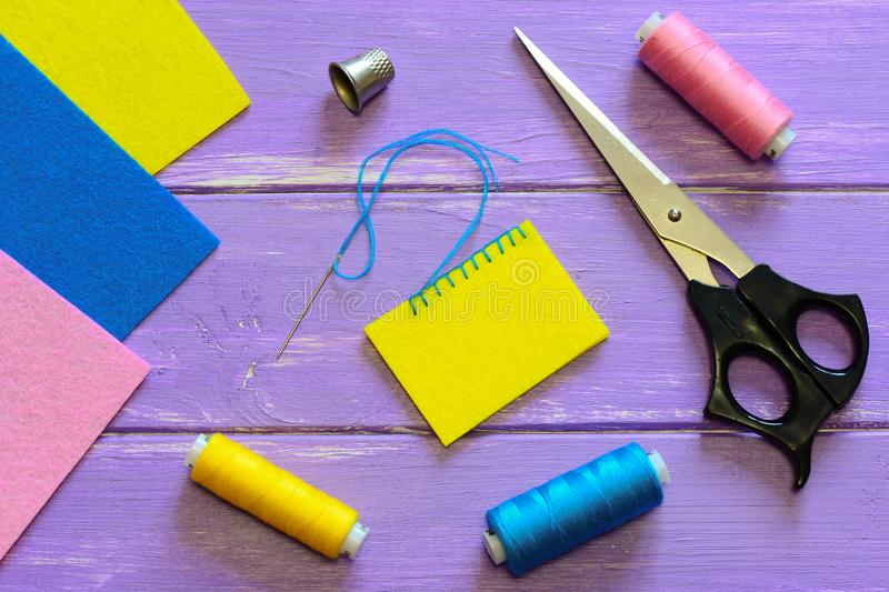 Closed blanket stitch by hand. Easy blanket stitch pattern. Colourful felt sheets, thread set, thimble, scissors. Sewing basics. How to sew a button. How to sew royalty free stock image