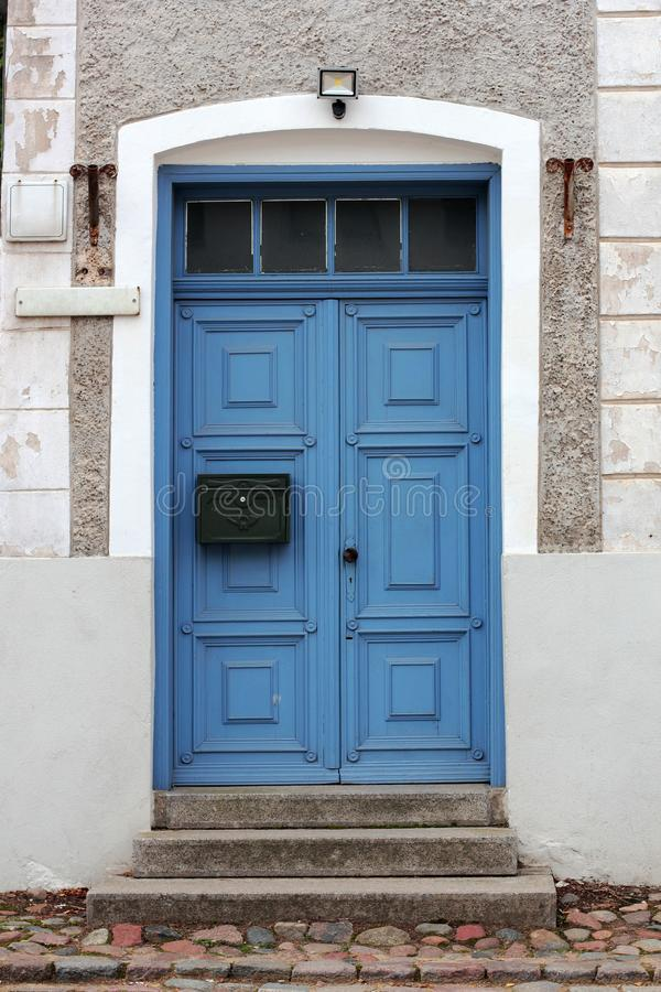Closed blue door with the mailbox in a stone house.  royalty free stock images