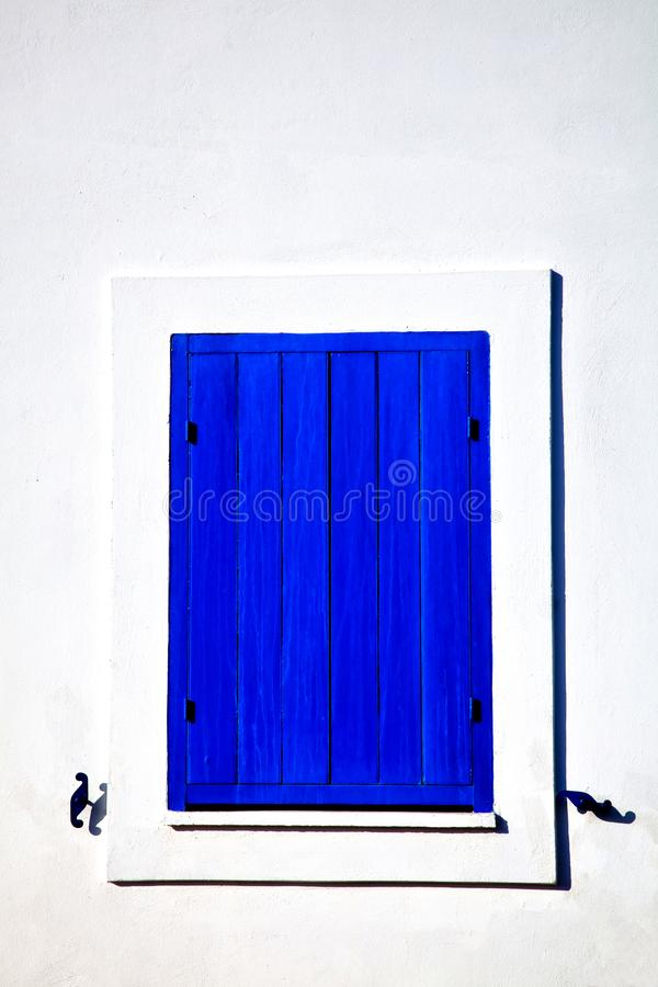 Closed blue window on a white wall in cycladic style royalty free stock images