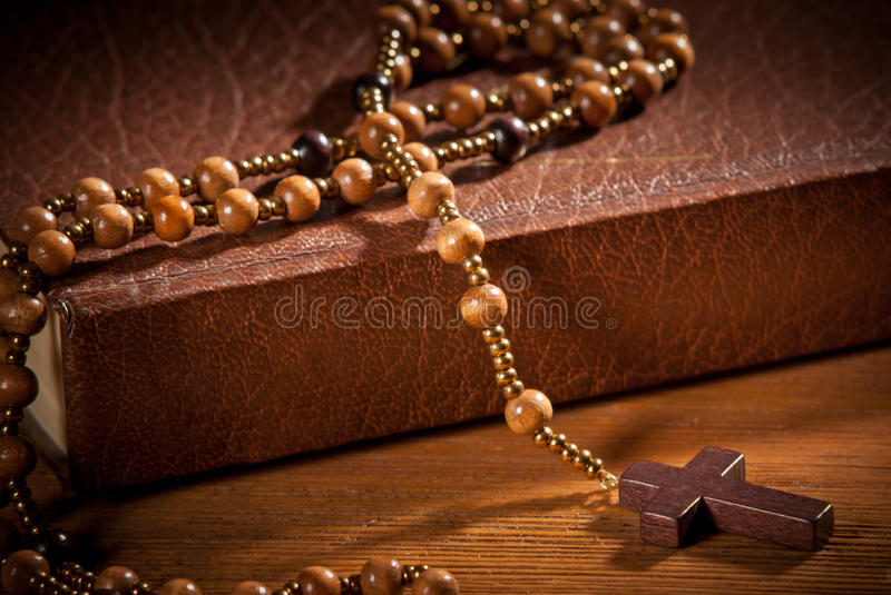 Closed book with rosary. On the wooden desk royalty free stock photo