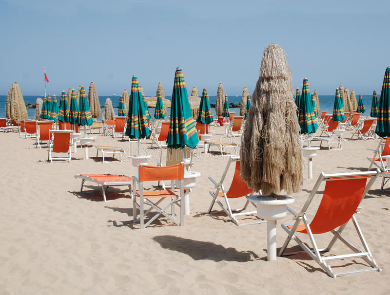 Closed Brown Beach Umbrellas, Abruzzo. A closed brown beach umbrella and deckchairs on a beach on a sunny summers day royalty free stock photos