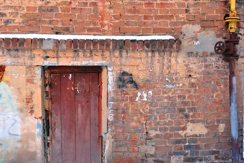 Closed brown painted door, red brick wall with yellow rusty gas pipe with spigot. Grunge horizontal background stock photo