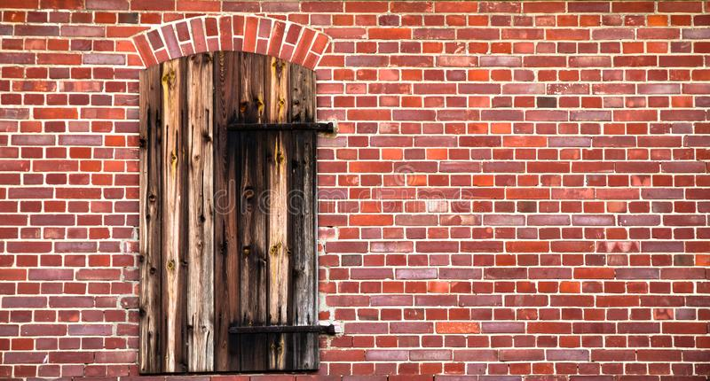 Closed brown red wooden door with rusted metal hinges on a grungy red brick wall of an old barn stock photography