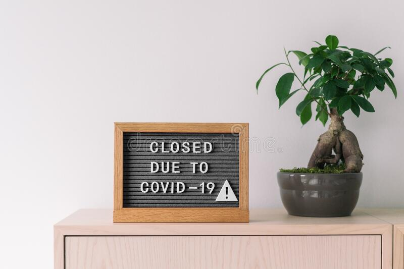 Closed business store due to COVID-19. Coronavirus lifestyle background with message sign at store front counter for stock photos