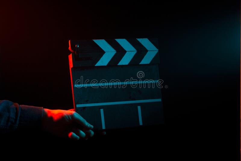 Closed clapperboard for cinema in hand, before filming on a black isolated background with red and blue backlighting royalty free stock photos