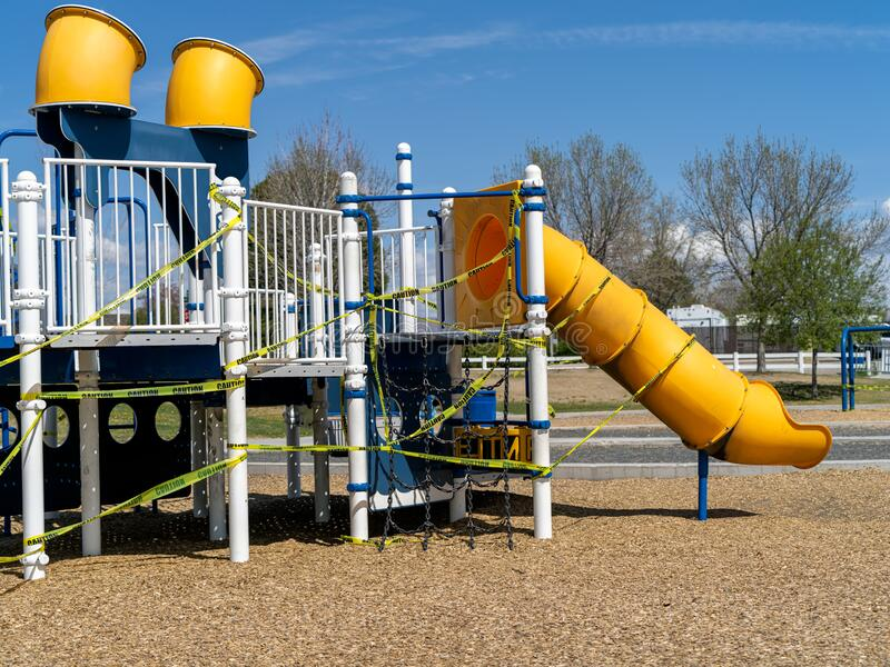 Closed down playground equipment amid the Covid-19, Coronavirus quarantine at a local park. Caution tape being used to close off a slide and other playground stock photography