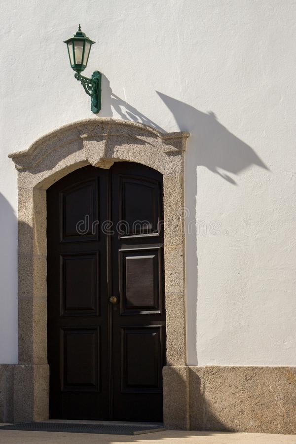 Closed entrance to the church with green lantern above the door. Street lamp on white wall of old building with wooden door. royalty free stock photography
