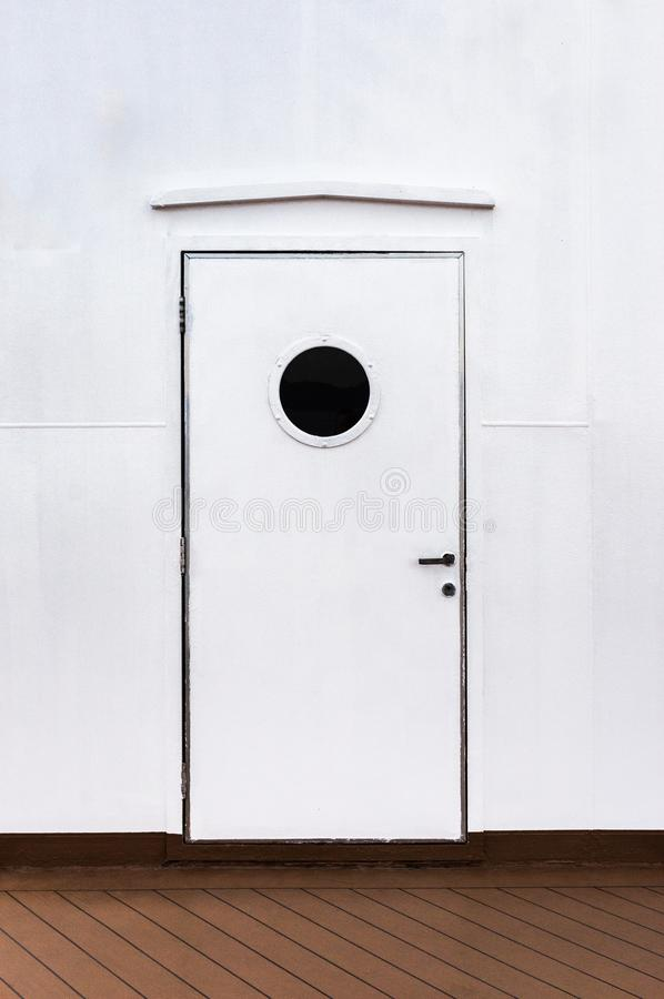 Closed exterior white metal door with round window on a cruise ship. royalty free stock photo
