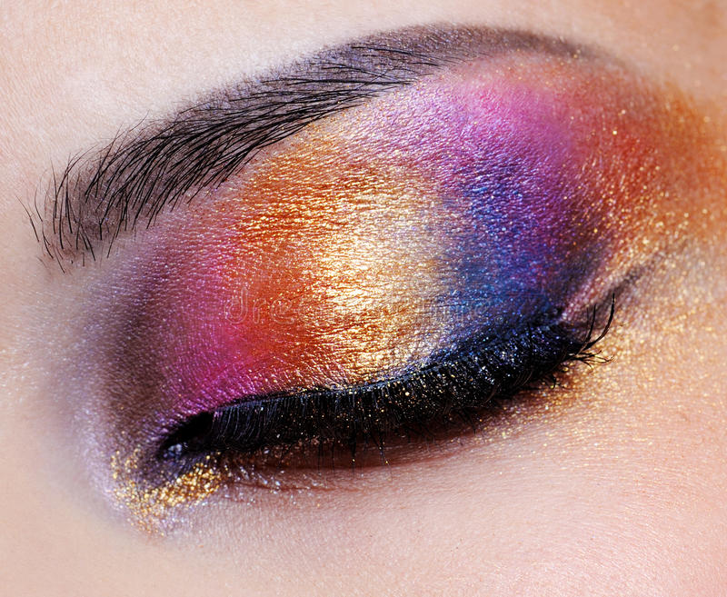 Closed eye with multicoloured eyeshadow. Human closed eye with multicoloured eyeshadow - macro shoot stock photo