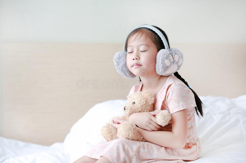 Closed eyes little Asian child girl wearing winter earmuffs and embracing teddy bear while sitting on the bed at home.  stock photo