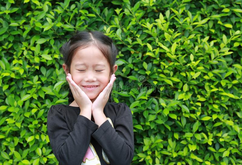 Closed eyes little Asian girl smiling and holds cheeks by hand against leaves wall background in the garden royalty free stock photography