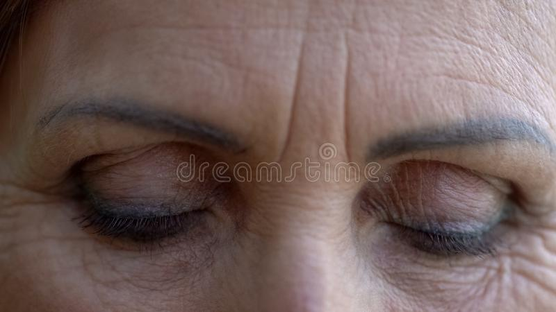 Closed eyes of wrinkled old woman, eyebrows and eyelids tattoo, beauty concept royalty free stock photo