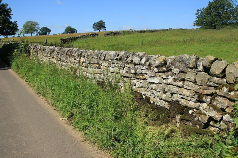 Closed fence and a large dry stone wall in the summer. Blue sky with clouds, trees, a closed fence and an old large dry stone wall at the countryside in England stock images