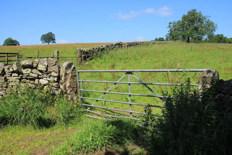 Closed fence and a large old dry stone wall in the summer. Blue sky with clouds, trees, a closed fence and an old large dry stone wall at the countryside in stock photography