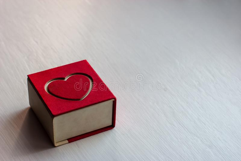 Closed gift box with a red heart cut in the lid on a light background. For a romantic gift for girls. Suitable for jewelry. White and red color boxes. Copy royalty free stock photography