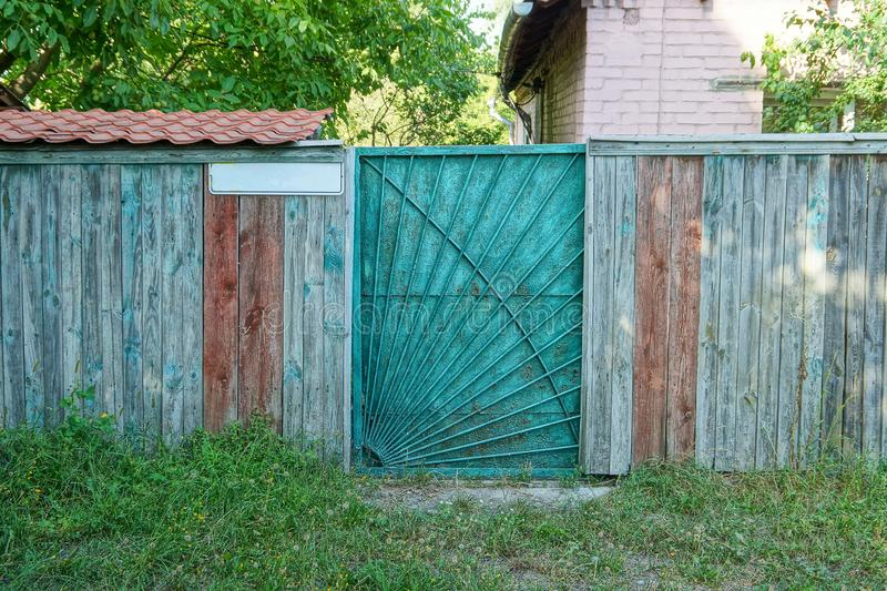 Closed green metal door and gray wooden fence on the street. In the grass royalty free stock photos