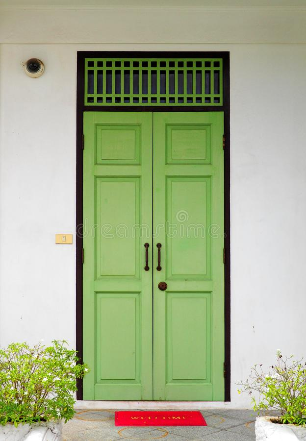Closed green wooden doors with red welcome mat royalty free stock images
