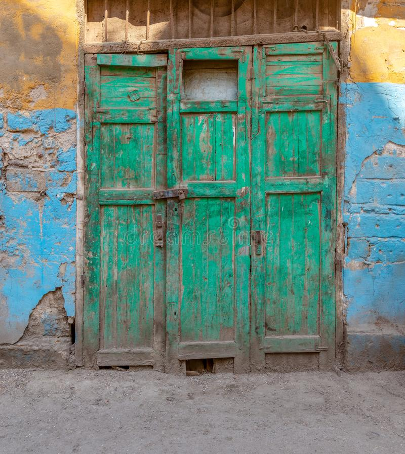 Green wooden grunge weathered abandoned door on dirty wall painted in yellow and blue stock images