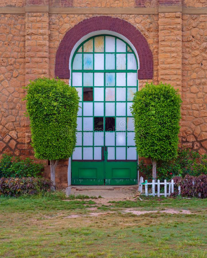 Closed grunge door with green metal grid framed by two green bushes in orange colored bricks stone wall in sunrise time royalty free stock photo