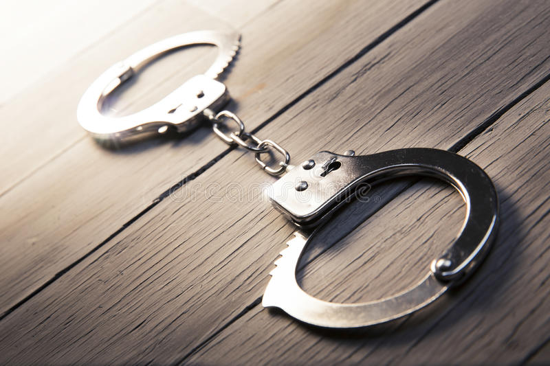 Download Closed Handcuffs On A Wooden Background Stock Photo - Image of police, guilty: 40360850