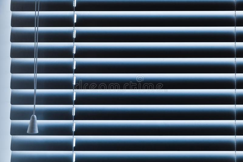 Closed horizontal blue window blinds. Closed horizontal window blinds, blue toned background photo royalty free stock image