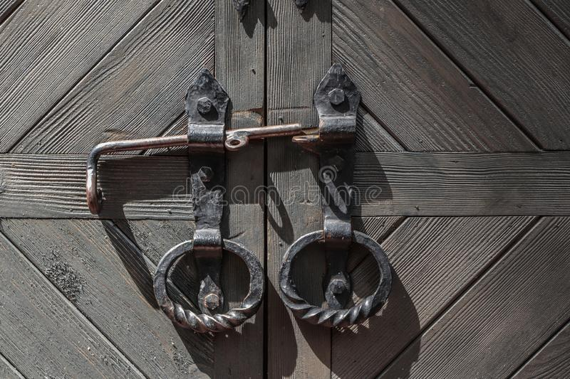 Closed large old door with round handles. Fragment. stock image