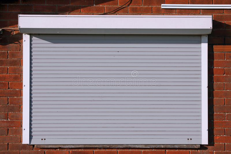 Closed light grey security shutters. Closed light grey serving hatch security shutters with brick background royalty free stock images