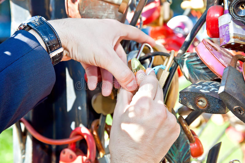 Closed lock and key thrown away - the key to a long and happy married life. Marriage. Tradition. The bride hangs a symbolic lock, secured a long and happy stock photo