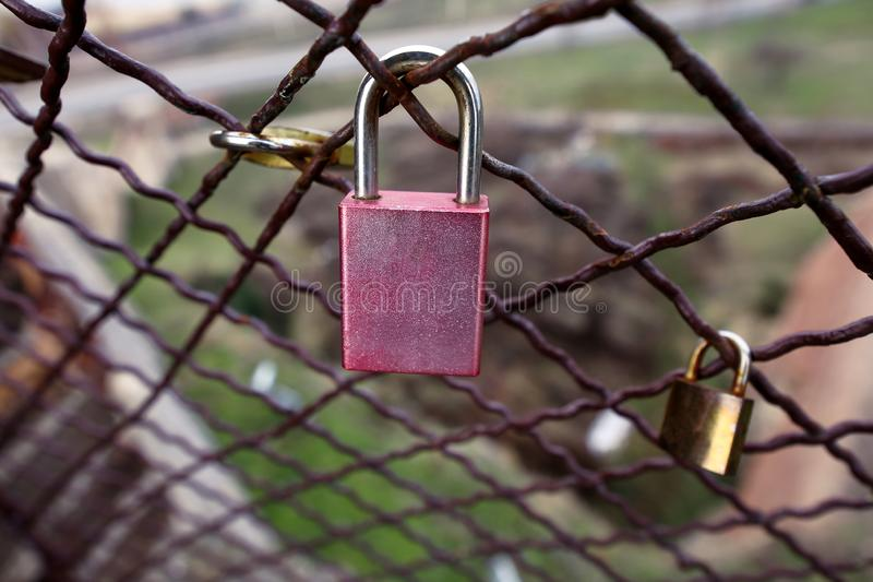 Closed love lock as symbol of eternal love with fence on bridge in city. Padlocks of lovers on bridge as symbol of connection. royalty free stock images
