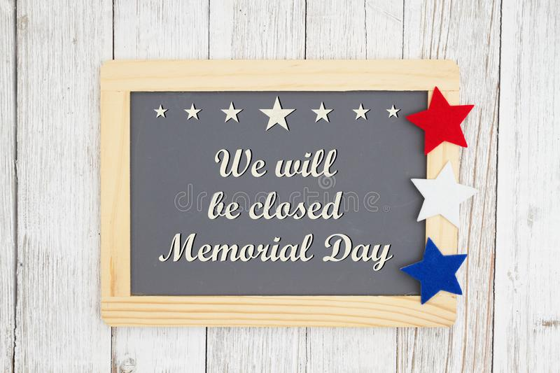 Closed Memorial  Day chalkboard sign. We will be closed Memorial Day text on a chalkboard with patriotic USA red and blue stars on weathered whitewashed royalty free stock image